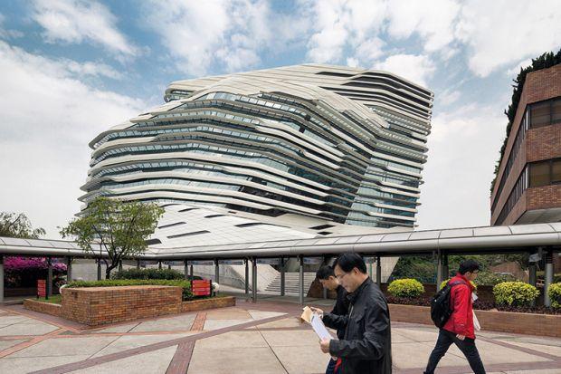 People walking past Jockey Club Innovation Tower, Hong Kong, China. Part of Hong Kong Polytechnic University