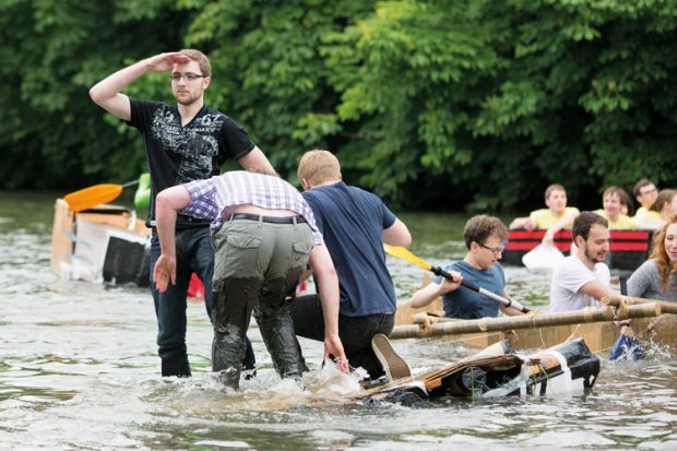 Cambridge University Students Cardboard Boat Race. A good captain never abandons his boat even as she goes down