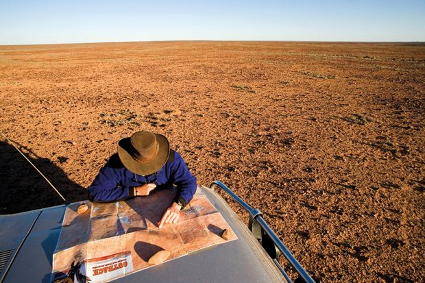 Man reading map on car bonnet in outback. Australia