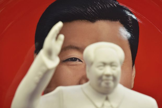 A decorative plate featuring an image of Chinese President Xi Jinping behind a statue of late communist leader Mao Zedong in a shop