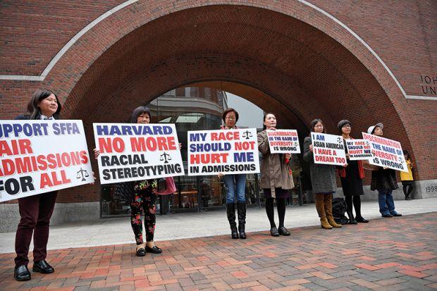 Demonstrators hold slogans in front of John Joseph Moakley United States Courthouse in Boston, Massachusetts