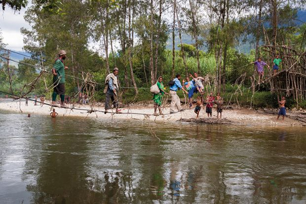 People cross a river in Papua New Guinea