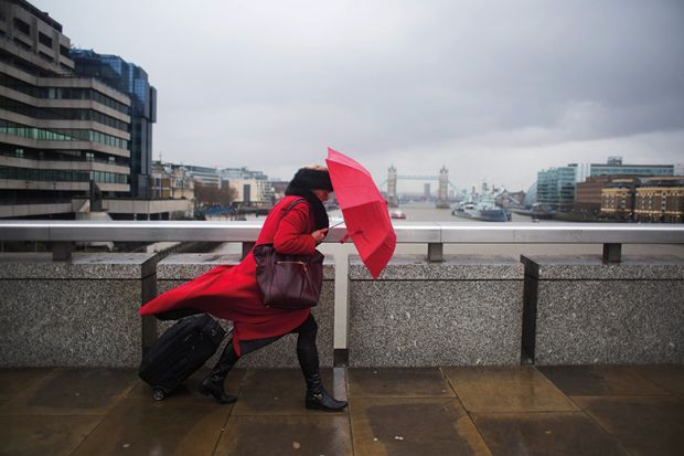 woman with umbrella walking across bridge, London