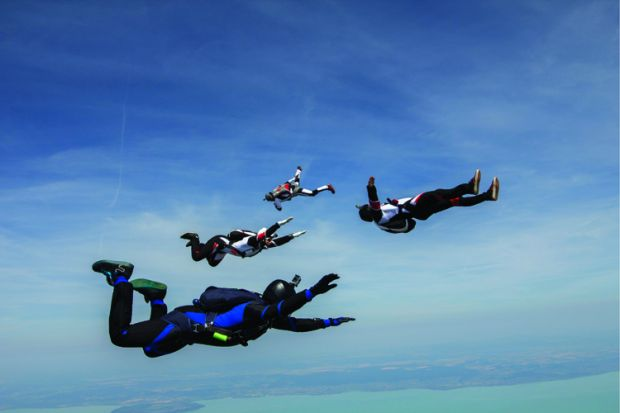 Four young adult male skydivers free falling