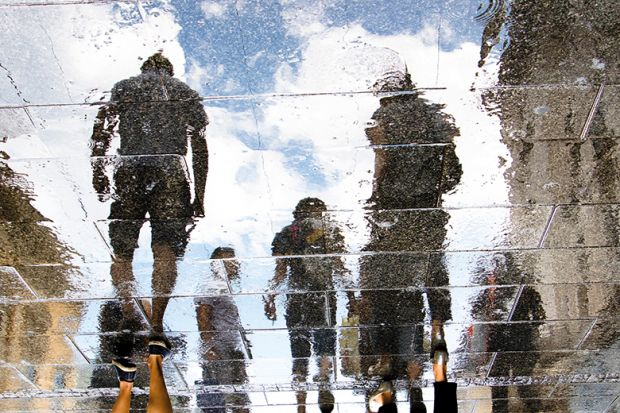 Reflection of human figures on a pavement