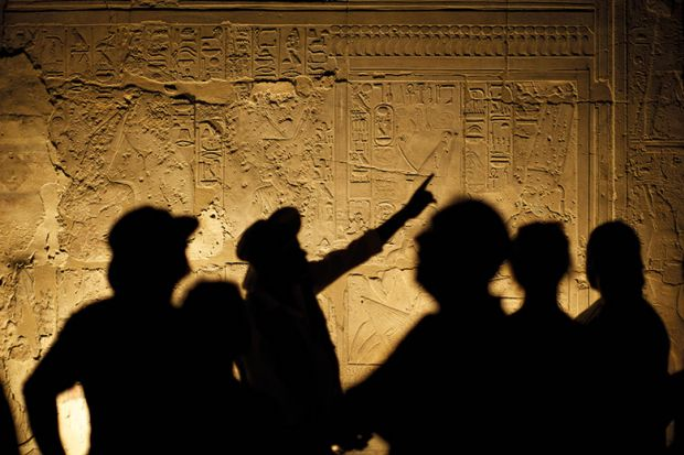 Egyptian Hieroglyphs with Tourist Archeologist Silhouettes