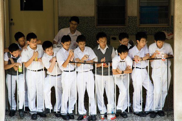 School boys watch a basketball game