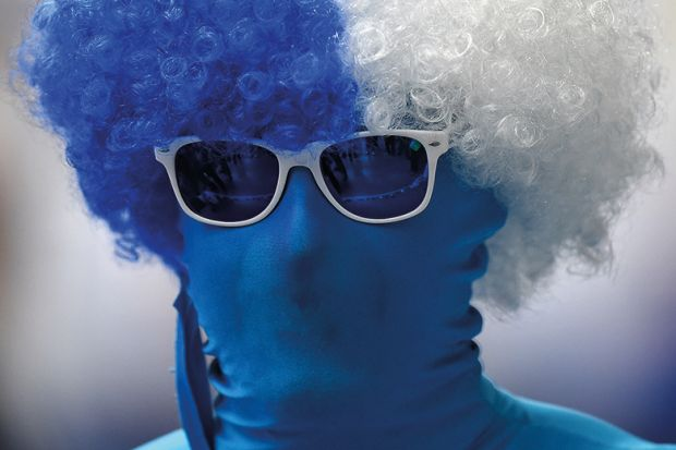 Person wearing morph suit and curly wig in Finland flag colours