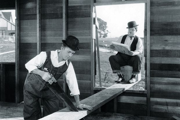 Laurel and Hardy sawing a plank of wood