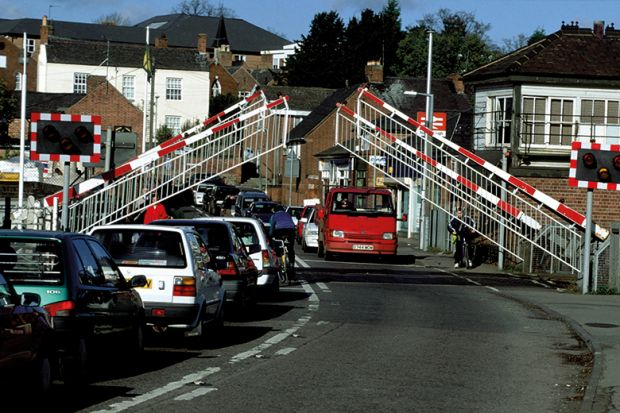 Barriers lifting at level crossing and waiting traffic streaming through
