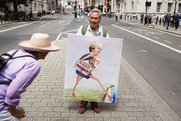 A woman looks at a painting by political artist Kaya Mar on Whitehall ahead of the pro-EU 'March for a People's Vote' in London