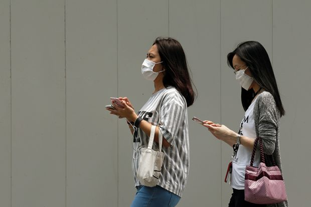 people wearing face masks and using mobile phones in Singapore