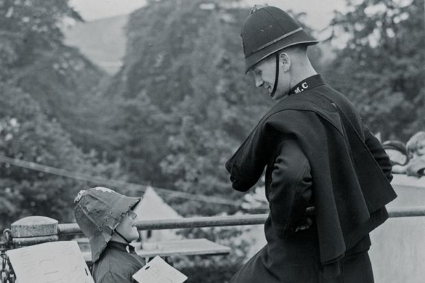 Policeman And Boy Wearing Police Costume