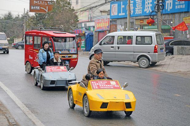 A farmer and his wife drive his miniature home-made Lamborghini. China