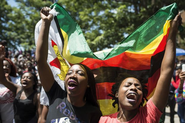 Women holding a flag of Zimbabwe in a demonstration at the University of Zimbabwe