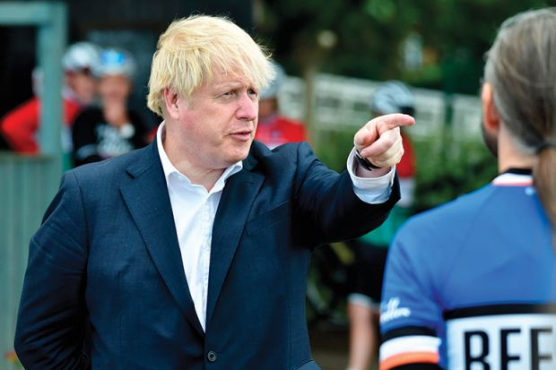 Britain's Prime Minister Boris Johnson (L) gestures as he talks to members of a local cycling club at the Canal Side Heritage Centre in Beeston, central England, on July 28, 2020