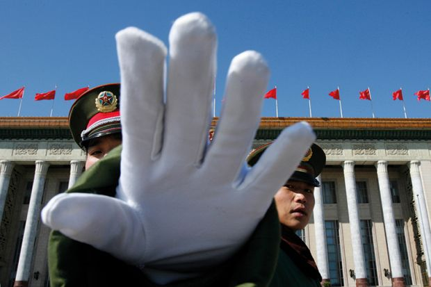A Chinese paramilitary policeman gestures towards a photographer to stop taking pictures while standing guard at the Great Hall of the People, Beijing