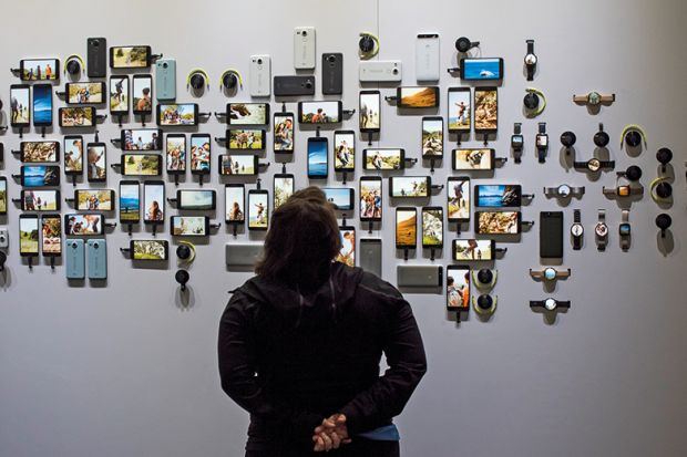 A person looking at various smart phones