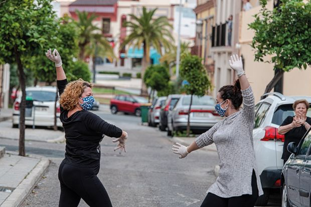 Locals wearing protective mask dance sevillana, a typical flamenco dance, in the street in front of their house April 24, 2020 in Mairena del Alcor, Spain during Covid-19 pandemic