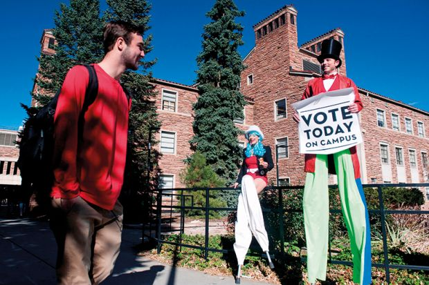 Person on stilts encourages students on the University of Colorado campus to vote