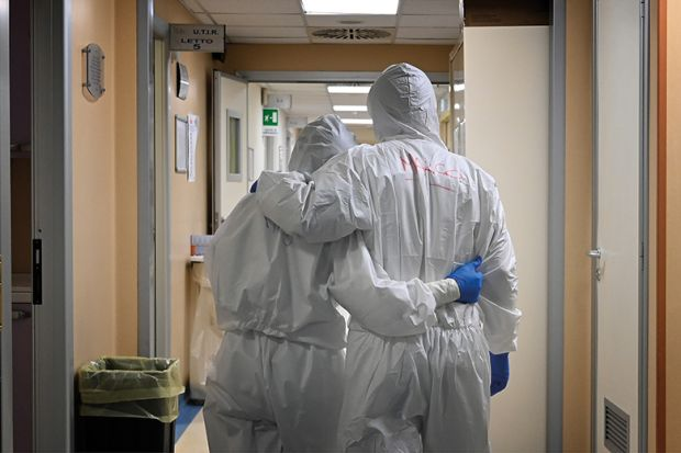 Doctor and nurse at the end of their shift in a corridor of the intensive care unit, treating COVID-19 patients. Italy.