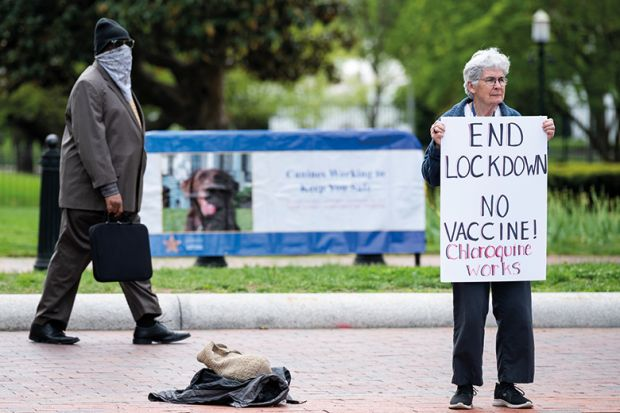 A lone protester holds a sign calling for an end to the lockdown and claiming chloroquine works as she stands in front of the White House in Washington on Saturday, April 25, 2020.
