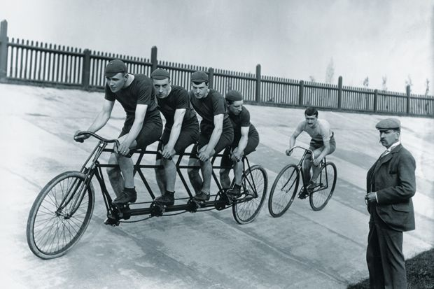 A four-man cycling tandem team in training with the 'chase and pacemaker' whilst being timed on the stopwatch.