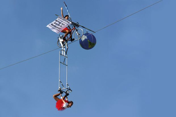 Tightrope artists balance a globe