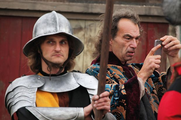 Background actor takes a picture using a smart phone next to another background actor dressed as a medieval guard