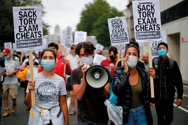 Students hold a placards as they march in central London on August 14, 2020 to protest against the downgrading of A-level results