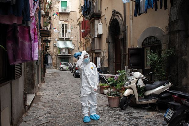 A healthcare worker wearing a protective suit walks through the Quartieri Spagnoli (Spanish Quarters) to screen people for coronavirus (Covid-19) during the pandemic. Italy