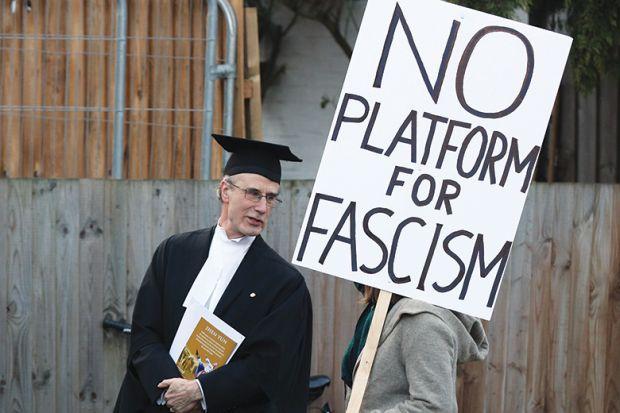 "A proctor speaks to a protester holding a ""No platform for fascism"" placard"