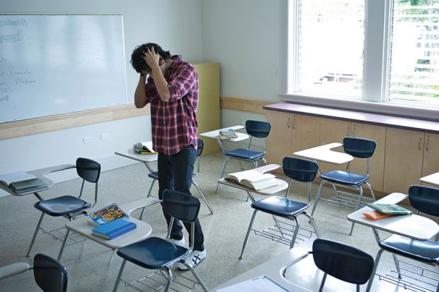 student in classroom with head in hands