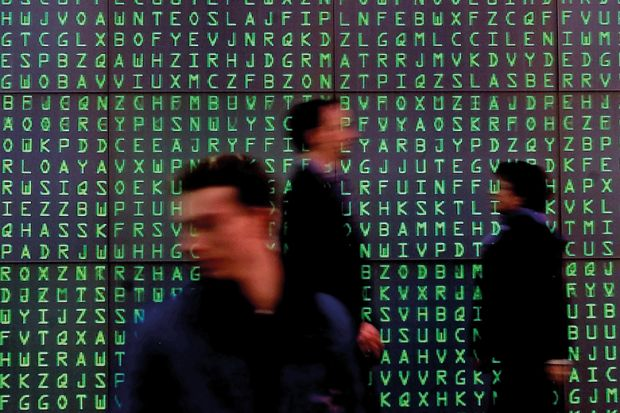 Visitors pass a giant Videoscreen with moving letters symbolising security codes at the computer- fair Cebit in Hanover