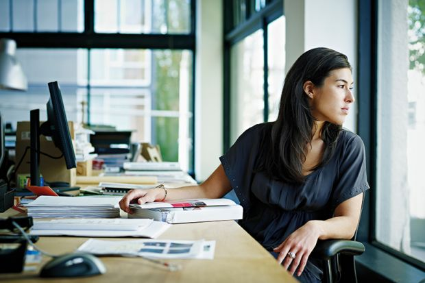 Woman looking out of window whilst at desk