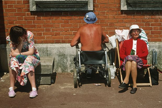 Ageing, elderly parents sunbathe with a teenage daughter as the father oddly faces a brick wall while sat in his wheelchair. Looking bored with the family holiday, the young lady of about 18 years of age, sits on a concrete block