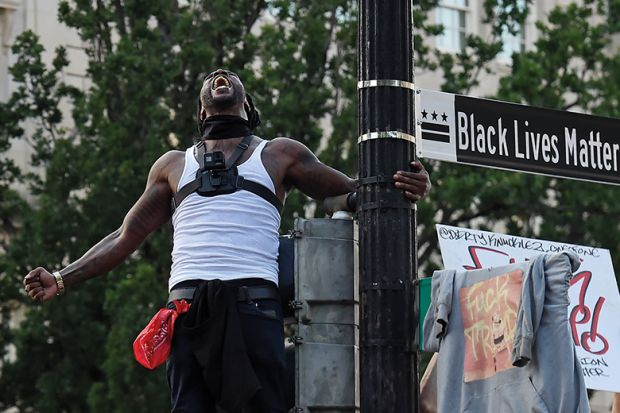 Man screams near a street sign that has been renamed 'Black Lives Matter Plaza' near the White House  during a demonstration against racism and police brutality, in Washing
