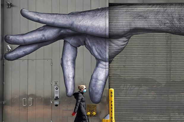 A woman in a mask walks past a mural of a hand on the side of a building in Midtown New York City  April 22, 2020