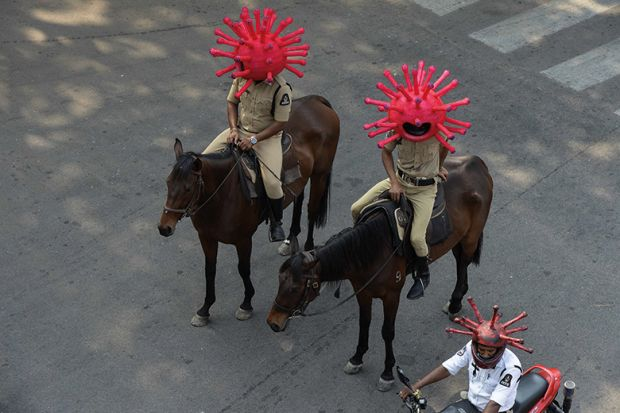 Police personnel wearing coronavirus-themed helmets ride on horses as they participate in a awareness campaign during a 21-day government-imposed nationwide lockdown as a preventive measure against the COVID-19 coronavirus. India