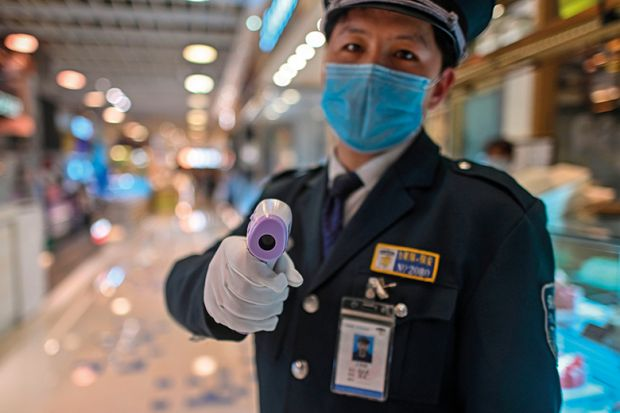 A guard wearing a facemask amid concerns over the spread of the COVID-19 novel coronavirus, holds a thermal gun to check the body temperature of visitors at the entrance of a restaurant area in Shanghai, on March 21, 2020.