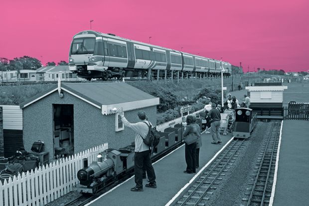 Miniature railway next to real train