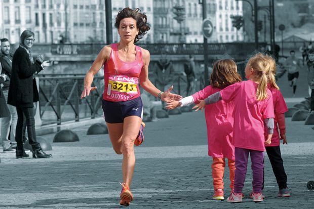 A female runner giving children a high five as she runs past.