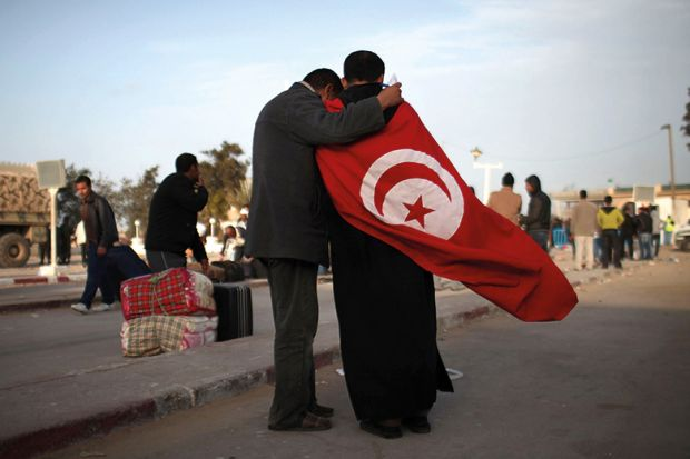 Two men, one wearing the flag of Tunisia, stand at the border of Libya on February 28, 2011 in Ras Jdir, Tunisia
