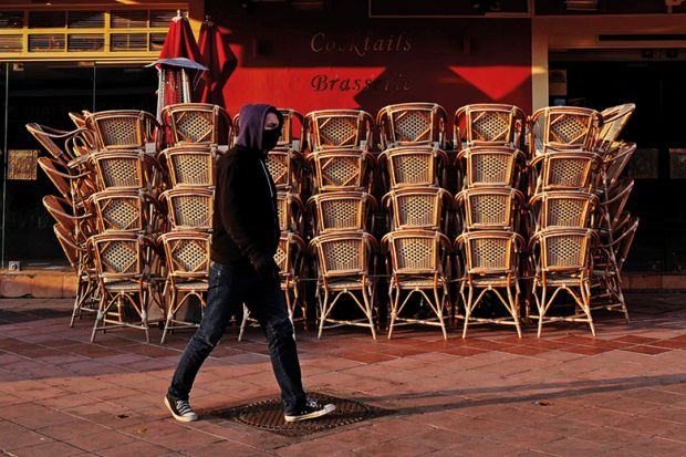 Man with facemask walking past closed cafe during coronavirus pandemic. France.