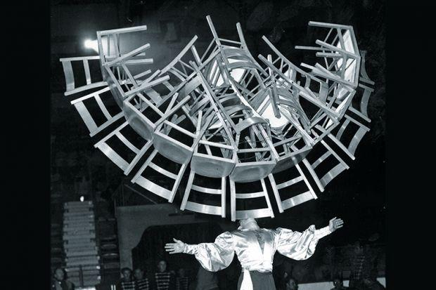 Man balancing lots of chairs