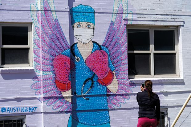 A woman shoots a picture of a mural depicting a medical worker with a mask covering her mouth and nose, wearing boxing gloves and angel-like wings on her back is seen on April 14, 2020 in downtown Denver, United States