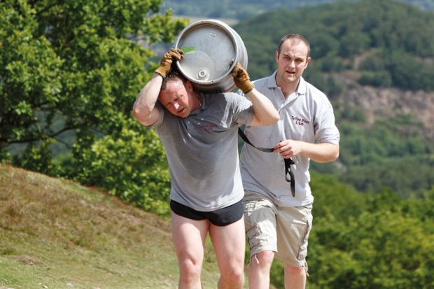 Tired man carrying beer barrel uphill