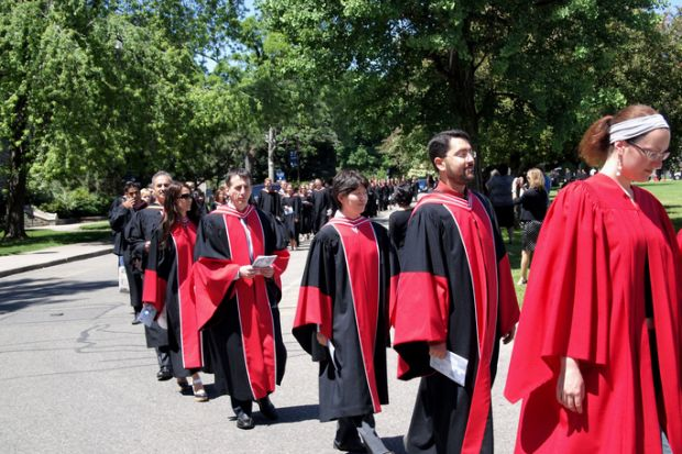 Toronto, Canada, June 8, 2010. Graduates at the University of Toronto walking to the ceremony where they will receive their diplomas. The red striped gowns indicate that they will receive doctorates