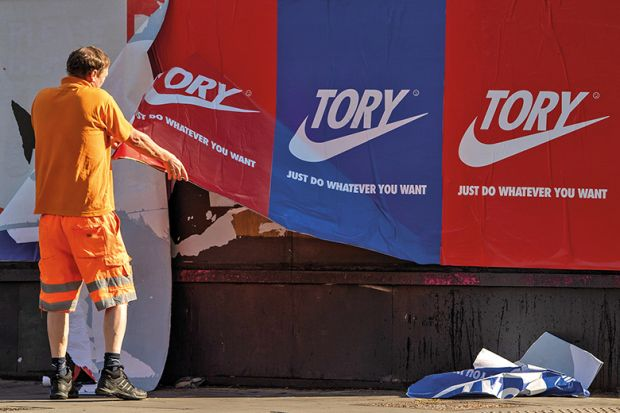 A maintenance worker removes posters depicting the Nike logo and reading 'Tory just do whatever you want' from a wall in Shoreditch, East London, on May 30, 2020, England.