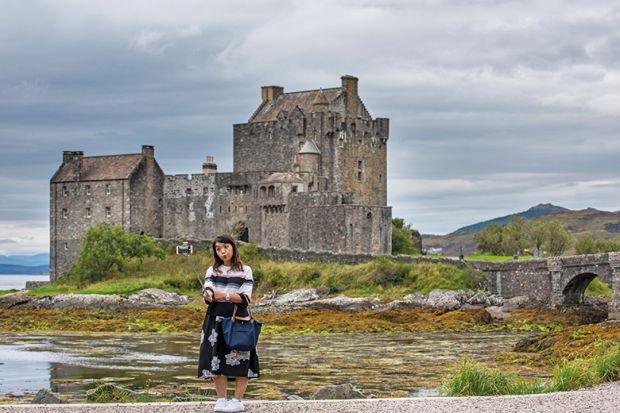 Tourist taking selfie at Eilean Donan Castle